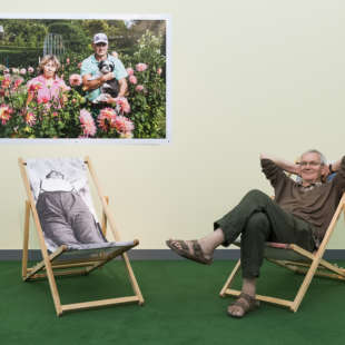 Photographer Martin Parr is sitting on a deck chair in front of a yellow wall with a photo of him hanging on it in his exhibition