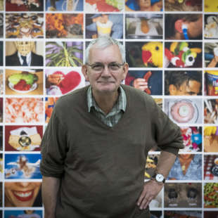 Martin Parr is standing in front of a wall on which many colorful pictures of him are hanging and bends slightly forward