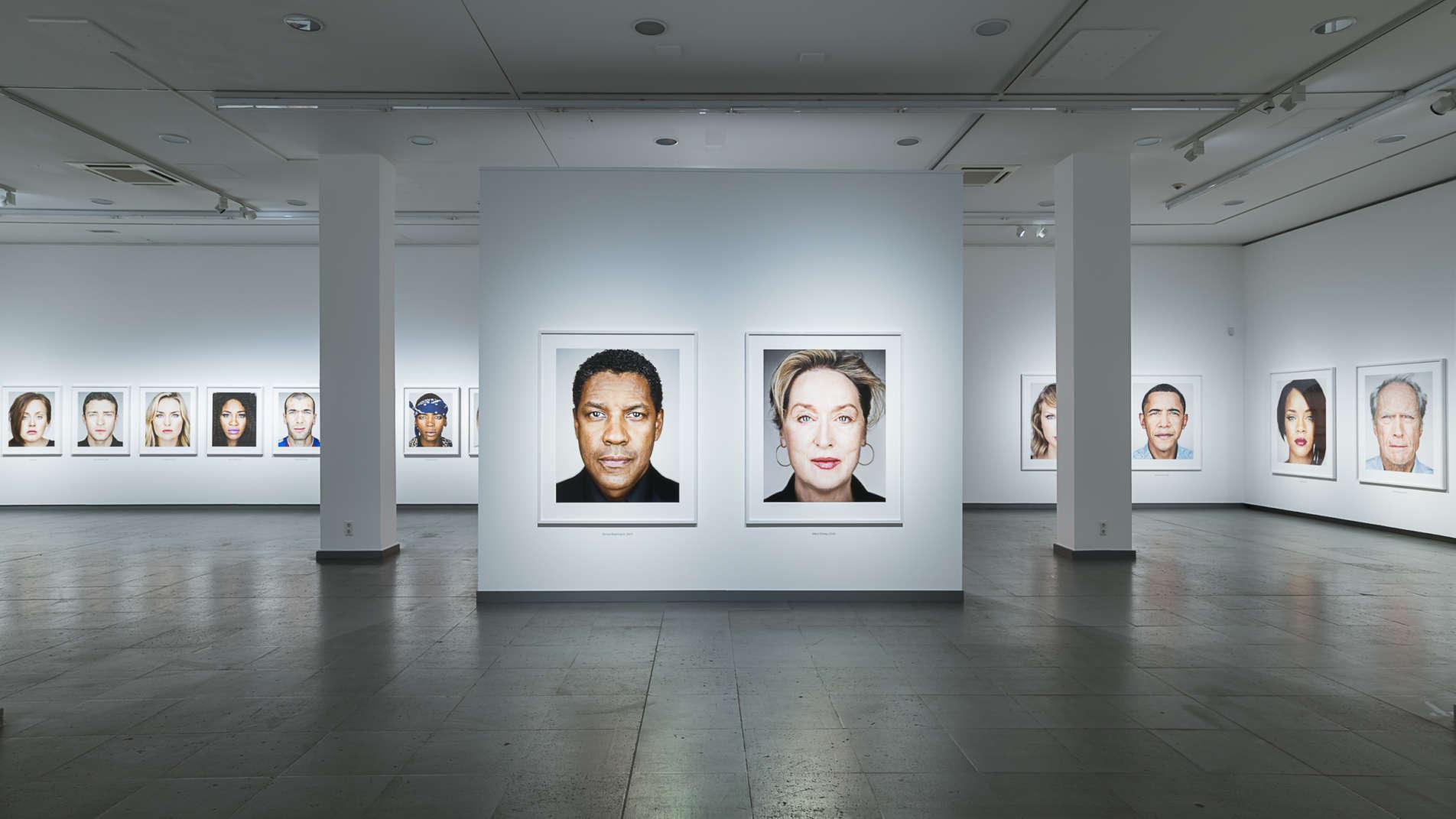 Ausstellungsansicht der Serie Close Up aus der Ausstellung Martin Schoeller mit gleichgestalteten Kopfporträts von Prominenten nebeneinander hängend