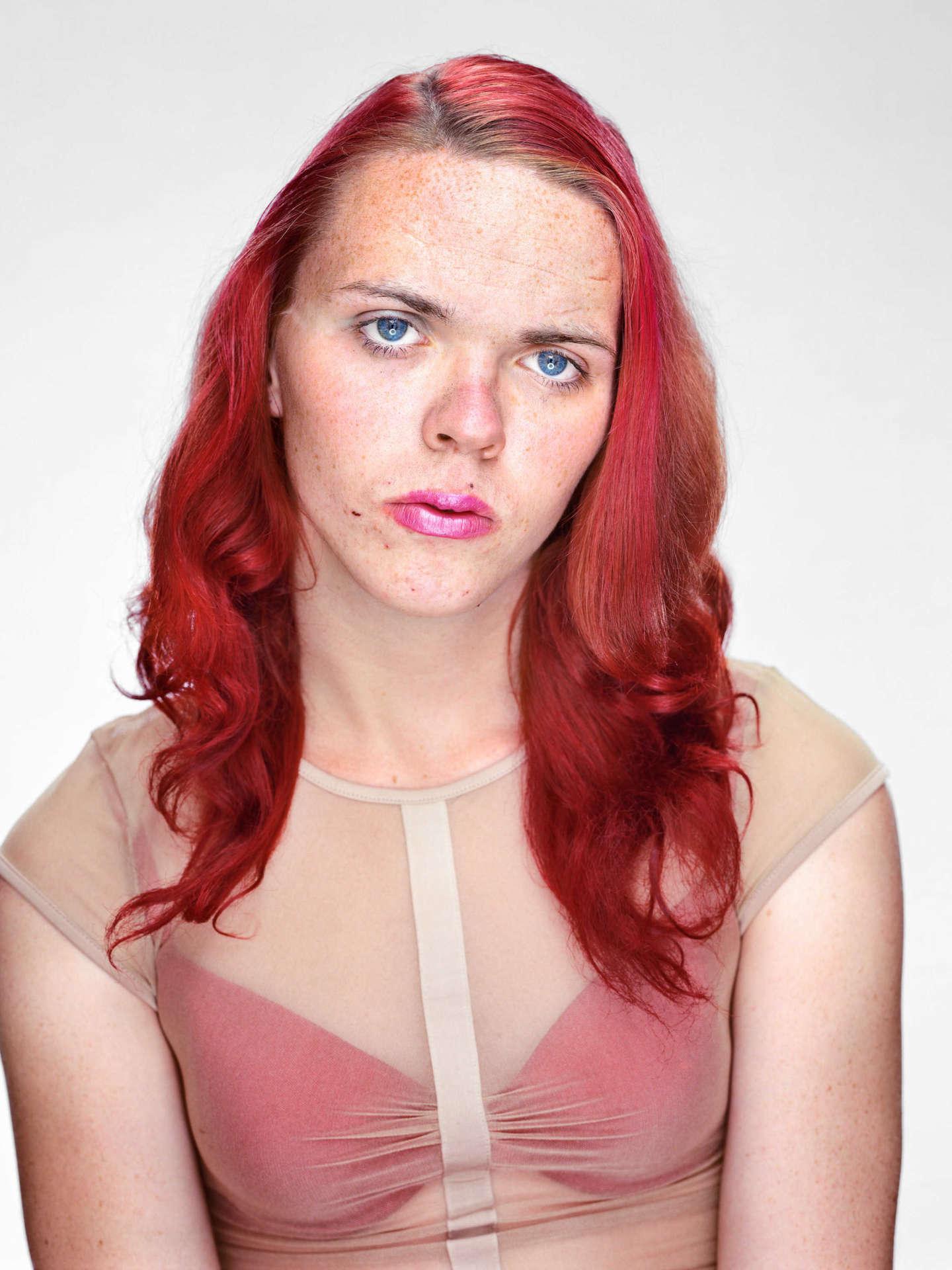 Halbporträt einer Person in Frontalansicht mit blauen Augen, Sommersprossen, langen, rotgefärbten Haaren und durchsichtigem Oberteil mit rotem BH