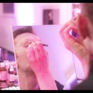 Die Drag Queen Lola Lash schminkt sich in einem Spiegel, der auf einem Tisch steht, auf dem Schminkutensilien liegen