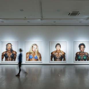 Eine Person läuft in der Ausstellung Martin Schoeller an mehreren großformatigen Fotos aus der Serie female bodybuilders vorbei