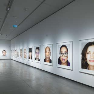 Eine Frau betrachtet Fotos von Prominenten aus der Serie Close Up in der Ausstellung Martin Schoeller