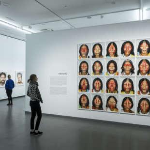 Ausstellungsansicht der Serie Kayapo aus der Ausstellung Martin Schoeller mit mehreren gleichgestalteten Porträts von indigenen Frauen in Blockhängung