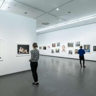 Zwei Personen betrachten Fotografien von Prominenten aus der Serie Portraits in der Ausstellung Martin Schoeller