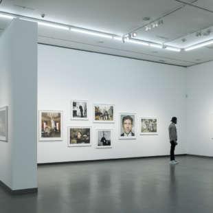 Ein Mann betrachtet Fotografien von Prominenten aus der Serie Portraits in der Ausstellung Martin Schoeller