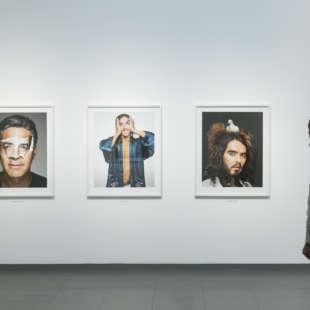 Ausstellungsansicht mit einem Mann, der drei Porträts aus der Serie Portraits in der Ausstellung Martin Schoeller betrachtet