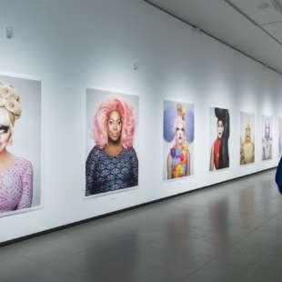 Eine Frau betrachtet großformatige Fotografien von Drag Queens in der Ausstellung Martin Schoeller