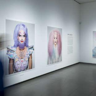 Eine Person läuft in der Ausstellung Martin Schoeller an Bildern aus der Serie Drag Queens vorbei