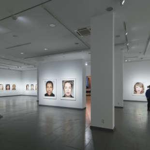Ausstellungsansicht der Serie Close Up in der Ausstellung Martin Schoeller mit zwei Personen, die die Bilder betrachten