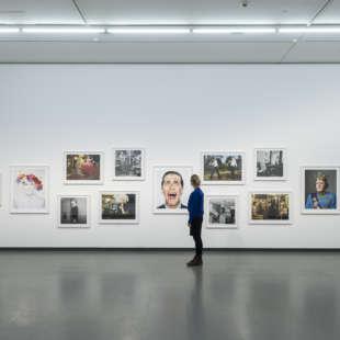 Eine Frau betrachtet mehrere Porträts von Prominenten aus der Serie Portraits in der Ausstellung Martin Schoeller