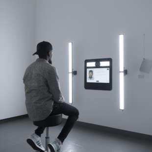 Ein Mann sitzt vor einem Bildschirm mit Kamera, mit dem er ein Foto von sich macht und dabei von zwei seitlich angebrachten Lampen beleuchtet wird