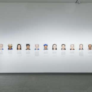 Eine Frau betrachtet mehrere kleine Porträtfotografien von freigesprchenen Todeszelleninsassen in der Ausstellung Martin Schoeller
