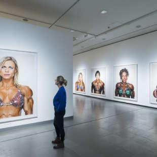 Eine Frau betrachtet Fotos von weiblichen Bodybuilderinnen in der Ausstellung Martin Schoeller