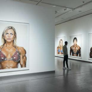 Ein Mann steht in der Ausstellung Martin Schoeller und betrachtet großformatige Fotografien aus der Serie Female Bodybuilders