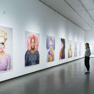 Ausstellungsansicht der Serie Drag Queens aus der Ausstellung Martin Schoeller mit großformatigen Fotos von Drag Queens und einer Besucherin