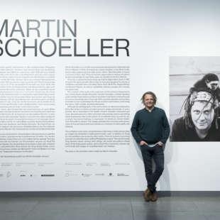 Fotograf Martin Schoeller in seiner Ausstellung im NRW-Forum vor Eingangswandtext und Foto von ihm selbst mit Affen auf dem Kopf
