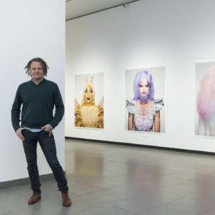 Fotograf Martin Schoeller steht vor Fotografien der Serie Drag Queens in seiner Ausstellung im NRW Forum