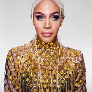 Drag Queen Trinity K Bonet mit blonden, zu einem Zopf gebundenen Haaren und lila Augenbrauen in einem mit gelben Steinen besetzten Oberteil