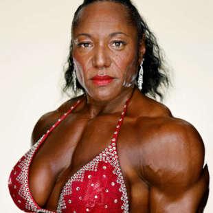 Halbporträt einer Bodybuilderin im Halbprofil mit schwarzen Haaren, glitzernden Ohrringen, rotem Lippenstift und rotem, strassbesetztem Bikinioberteil