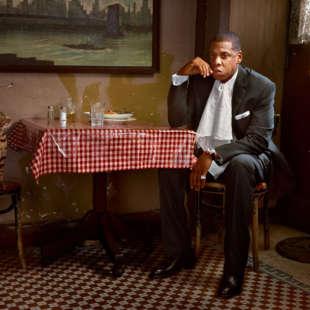 Musiker Jay-Z im Anzug sitzt mit einer Katze an einem Tisch mit einer rot weiß Karierten Tischdecke vor einer Wand an der ein Gemälde hängt
