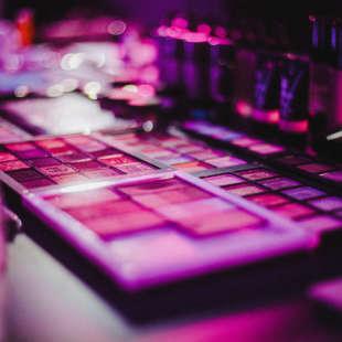 Schminkutensilien liegen auf einem Tisch und sind in lila und rosa Licht getaucht