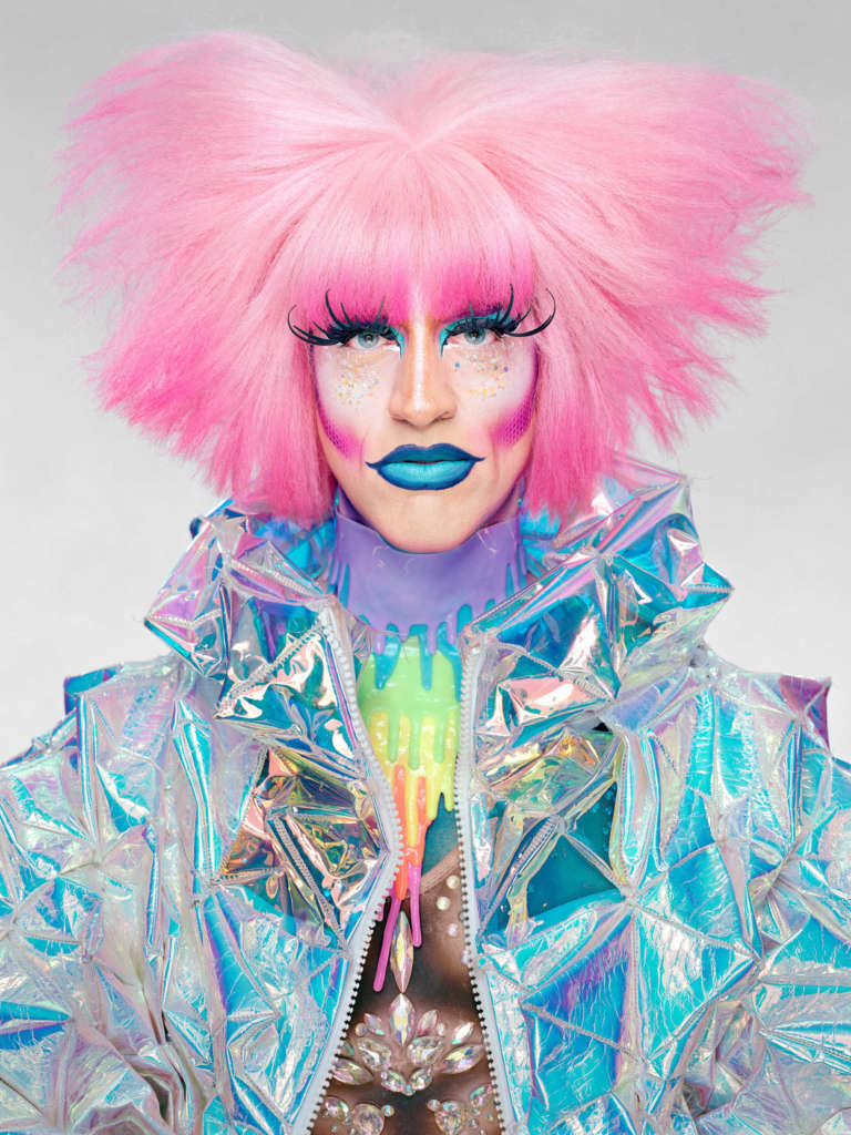 Drag Queen Acid Betty with pink hair, big eye lashes, blue lipstick and reflecting Jacket