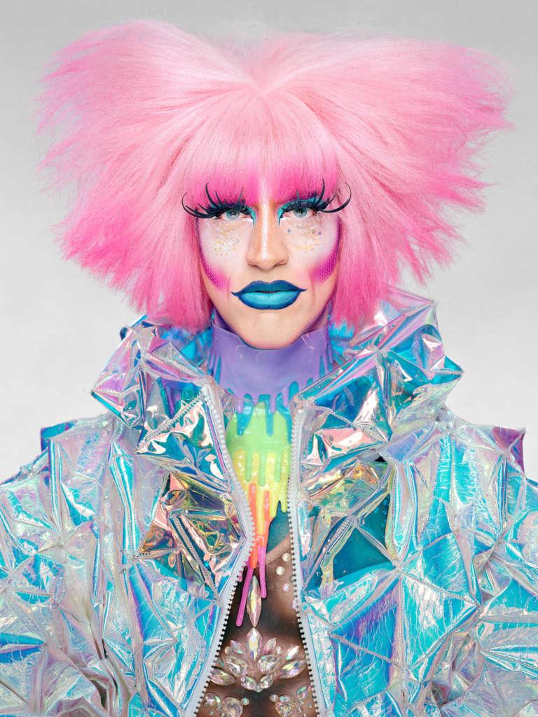 Drag Queen mit pinken Haaren, langen Wimpern, blau glänzenden Lippen, Glitzer-Make Up in einer Jacke aus reflektierendem Stoff vor weißem Hintergrund