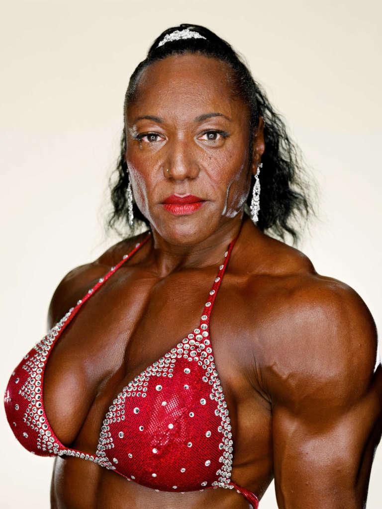 portrait of a bodybuilder in semi-profile with black hair, glittering earrings, red lipstick and red rhinestone bikini top
