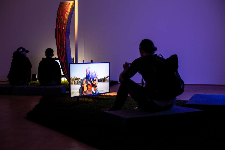 Drei Personen sitzen in einem dunklen Raum vor hell erleuchten Monitoren