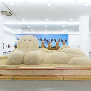 Ausstellungsansicht der Ausstellung Olaf Breuning mit einer großen, liegenden Skulptur aus Sand