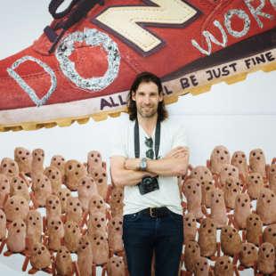 Olaf Breuning mit einer Kamera um seinen Hals hängend in seiner Ausstellung im NRW Forum vor einem Kunstwerk