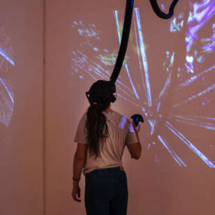 Woman standing in the Pendoran Vinci exhibition with VR glasses on her head and a controller in her hand, illuminated by projectors