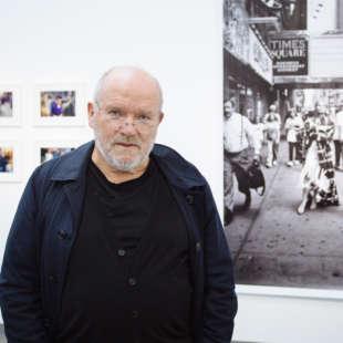 Der Fotograf Peter Lindbergh steht schwarz gekleidet in der Ausstellung Lindbergh Winogrand vor einer großen schwarz weiß Aufnahme und kleineren Fotos