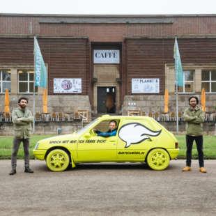 Ein gelbes Auto, in dem ein Mann sitzt, steht vor dem NRW Forum. Auf dem Auto steht: Sprich mit mir. Ich fahre dich