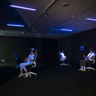 Drei Personen sitzen in der Ausstellung Whiteout auf Bürostühlen und haben eine VR Brille auf und werden dabei von Schwarzlicht angeleuchtet