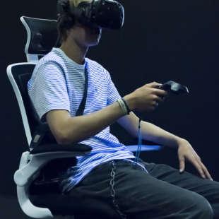Ein junger Mann sitzt auf einem Drehstuhl in der Ausstellung Whiteout mit einer VR Brille auf dem Kopf und wird von Schwarzlich beleuchtet