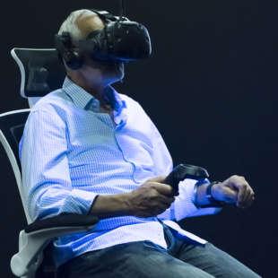 Ein älterer Mann sitzt auf einem Drehstuhl in der Ausstellung Whiteout mit einer VR Brille auf dem Kopf und wird von Schwarzlich beleuchtet