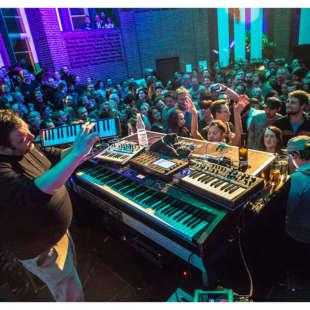 Musiker spielt auf einer Bühne im NRW Forum vor einem großen Publikum Melodica und hat auch andere Instrumente vor sich