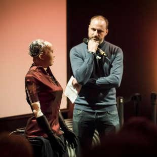 Alain Bieber, künstlerischer Leiter des NRW Forums, unterhält sich mit dem in rot gekleideten Roboter Sophia