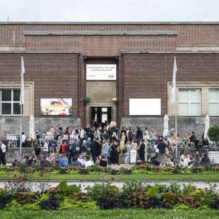 Eingangsbereich des NRW Forums von außen mit vielen Personen, die sich davor versammelt haben