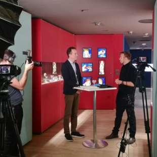 Zwei Personen stehen an einem Stehtisch in den Ausstellungsräumen des Kunstpalast und unterhalten sich während sie von einem Kamerateam gefilmt werden