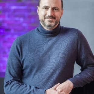 Hüftporträt von Alain Bieber, dem künstlerischen Leiter des NRW Forums, mit blaugrauem Rollkragenpullover