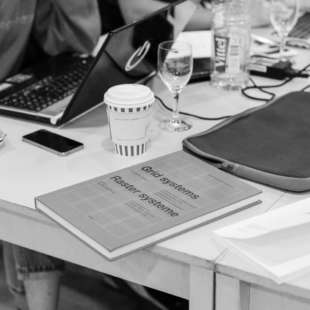 Ein Tisch an dem Personen sitzen und auf dem Laptops, Gläser, Kaffeebecher, Tassen, Laptophüllen und ein Buch mit der Aufschrift Raster systeme stehen