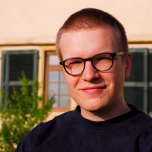 Porträt von Alexander Borowski mit Fenstern eines Hauses und einem Baum im Hintergrund