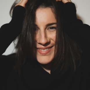 Porträt von Laura Greco, die sich in die Haare fässt und vor einem weißen Hintergrund steht
