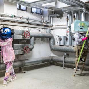 Maskottchen des NRW Forums Data und Zip in einem Heizungskeller vor Rohren und auf einer Leiter stehend