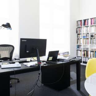 Arbeitszimmer mit schwarzem Schreibtisch mit Computer, Lampe und Unterlagen sowie einem Konferenztisch mit gelbem Stuhl und Bücherregal im Hintergrund