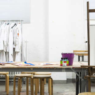Arbeitsraum mit Staffelei mit Bild, einem Tisch mit Hockern und Bastelutensilien sowie Arbeitskittel an einer Kleiderstange im Hintergrund