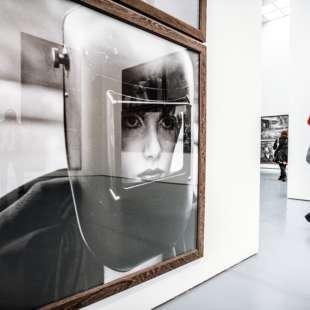 Ausstellungsansicht aus der Ausstellung Untold Stories im Kunstpalast mit schwarz weiß Foto auf der linken Seitee und einem Besucher auf der rechten.